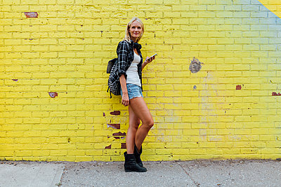Portrait of young woman with cell phone at yellow brick wall - p300m2069191 by Boy photography