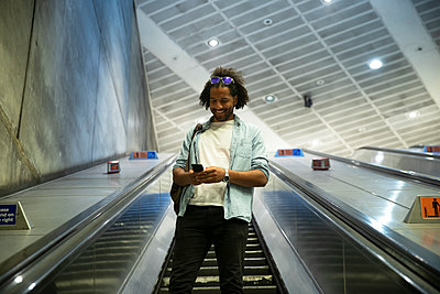 Young trendy man smiling while using smart phone on escalator at subway station - p300m2202954 by Pete Muller