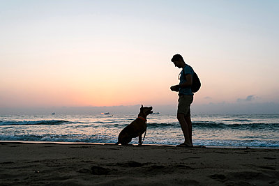 Silhouette man standing with his dog at the beach - p300m2206657 by Ezequiel Giménez