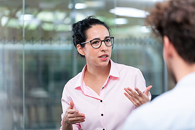 Female entrepreneur gesturing while talking to male colleague in office - p300m2265992 by Florian Küttler