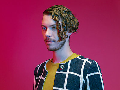 Portrait of fashionable dressed young man with curly hair in front of red background - p300m973541 by Rainer Holz