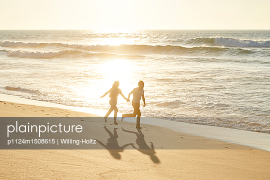 Young couple on beach - p1124m1508615 by Willing-Holtz