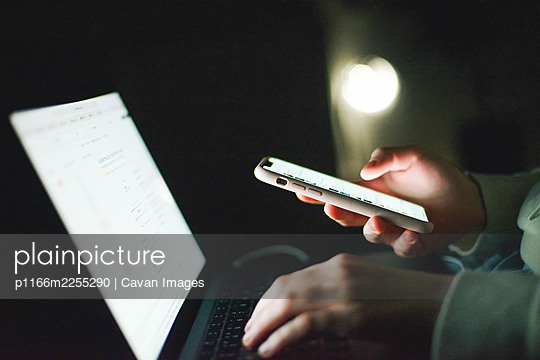 Anonymous woman working on laptop at night - p1166m2255290 by Cavan Images
