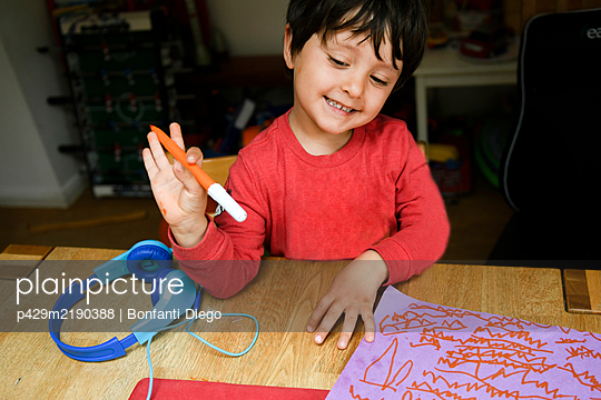 A five year old boy in blue headphones having an interactive learning session, home schooling.  - p429m2190388 by Bonfanti Diego