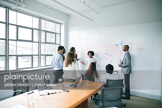 Businesswoman talking near whiteboard in meeting - p555m1504091 by John Fedele