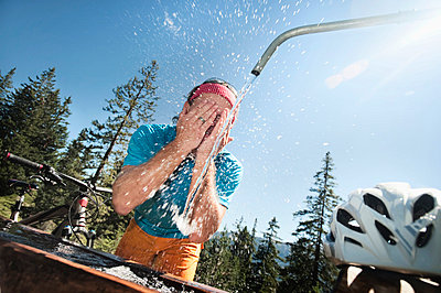 Mountain biker washing his face - p1026m786145f by Robert Niedring