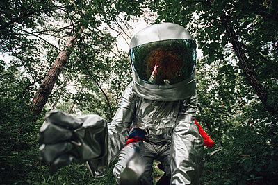 Spaceman exploring nature, examining plants in forest - p300m2030516 by Vasily Pindyurin