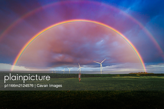 a small boy in a yard with a double rainbow - p1166m2124576 by Cavan Images