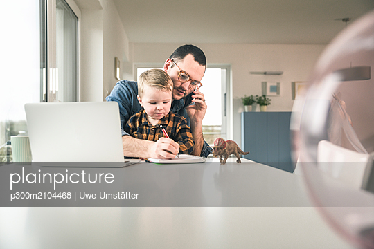 Busy father working at table in home office with son sitting on his lap - p300m2104468 von Uwe Umstätter