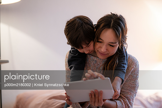 Mother and little son using digital tablet at home - p300m2180302 by Kniel Synnatzschke