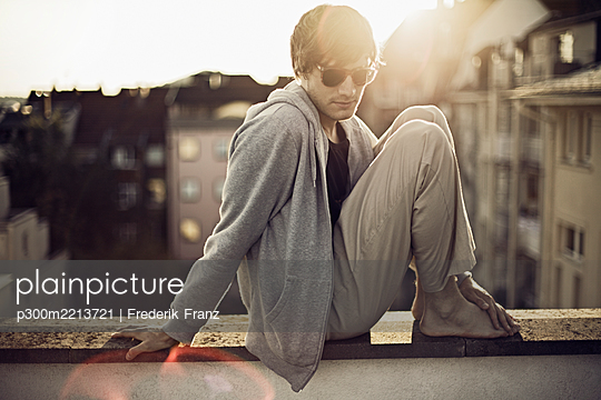 Germany, Baden-Wuerttemberg, Pforzheim, young man sitting on wall - p300m2213721 by Frederik Franz