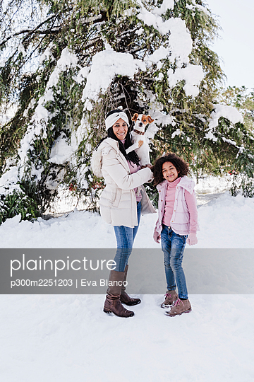 Happy family with dog standing in snow at park during winter - p300m2251203 by Eva Blanco