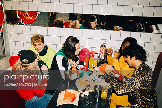 High angle view of male and female friends talking at table in cafe - p426m2194763 by Maskot