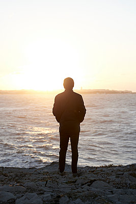 Man by the sea at sunset - p1124m1564788 by Willing-Holtz