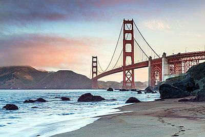 Golden Gate Bridge over sea against sky during sunrise - p1166m1230527 by Cavan Images