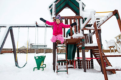 Playful girl jumping from outdoor play equipment at playground during winter - p1166m1542020 by Cavan Social