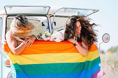 Two lesbian women have fun in a vintage classic van. - p1166m2073767 by Cavan Images