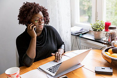 Woman on the phone using laptop - p312m1556954 by Susanne Kronholm