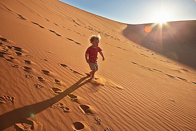 Boy walking on sand dune, Namib Naukluft National Park, Namib Desert, Sossusvlei, Dead Vlei, Africa - p429m1029676 by Stephen Lux