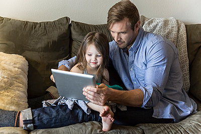 Father and daughter using digital tablet on sofa - p555m1311507 by Andie Mills