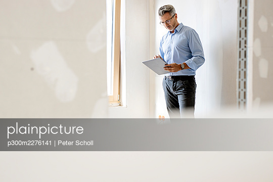 Male professional using digital tablet by wall at site - p300m2276141 by Peter Scholl