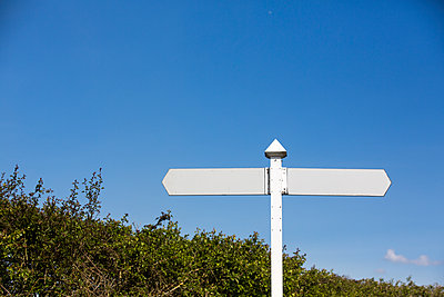 A white double sided signpost with no directions or words, a blank sign set against a deep blue sky in the summer sunshiine. - p1057m1332428 by Stephen Shepherd