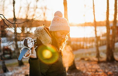 Portrait of a woman smiling holding skis at sunset - p1166m2153681 by Cavan Images