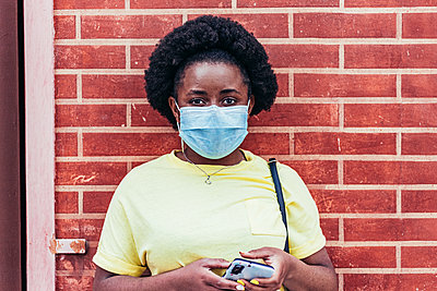 Portrait of Black African American Girl with face mask on red brick wall background. - p1166m2269122 by Cavan Images