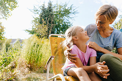 Mother and daughter having fun in garden - p300m2059043 by Kniel Synnatzschke