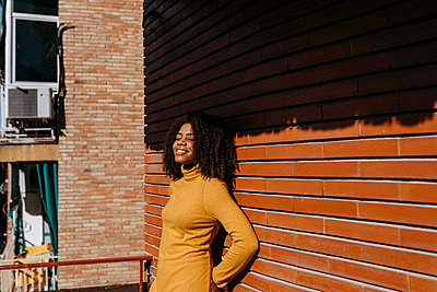 Smiling woman with hands behind back leaning on wall - p300m2256659 by Tania Cervián
