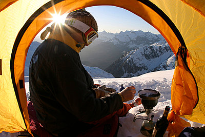 Mountaneer is boiling water and preparing the dinner on his multi fuel kitchen high up in the alps at sunset - p3433634 by Patrik Lindqvist
