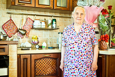 Older Caucasian woman standing in kitchen - p555m1413585 by Aleksander Rubtsov