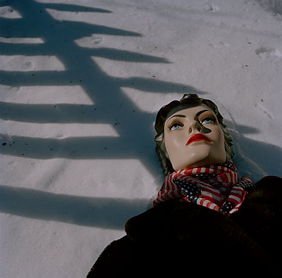 Mannequin Laying in Snow with Shadow of Picket Fence - p694m1192946 by Nancy Grace Horton