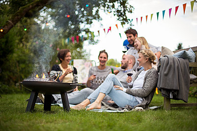 Clique having summer garden party - p788m1165280 by Lisa Krechting