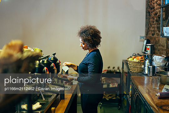 male waitress barista working in coffee shop. Prepare decorated coffee - p1166m2112462 by Cavan Images