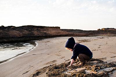 Kleiner Junge spielt am Sandstrand - p1046m1467514 von Moritz Küstner