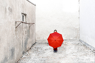 Child hidden behind red umbrella in a backyard - p1625m2228447 by Dr. med.