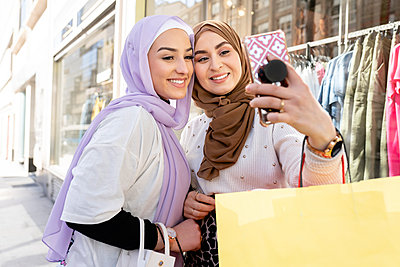 Female Arab friends in hijabs taking selfie through smart phone while shopping in city - p300m2275139 by Jose Carlos Ichiro