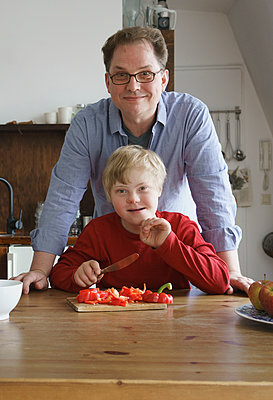 Portrait of father and boy at table in kitchen - p301m1180576 by Halfdark