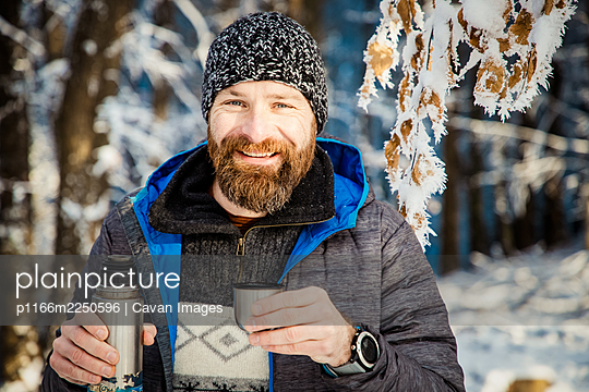 man drinking hot tea in winter forest - p1166m2250596 by Cavan Images