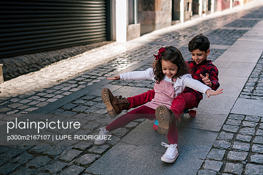 Boy and girl riding on skateboard down an alley - p300m2167107 by LUPE RODRIGUEZ