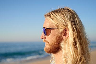 Mann mit Sonnenbrille am Strand, Porträt - p1124m1510658 von Willing-Holtz
