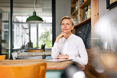 Portrait of confident blond woman sitting at table - p300m1459860 by Peter Scholl
