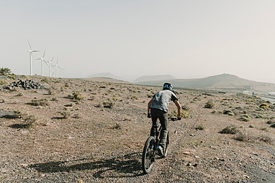 Spain, Lanzarote, mountainbiker on a trip in desertic landscape - p300m2102567 by Hernandez and Sorokina