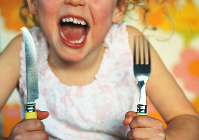 Girl holding up knife and fork - p6750034 by Mieke Dalle