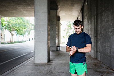 Young male runner checking smartwatch in underpass - p924m2074742 by JFCreatives