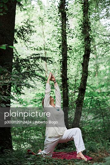 Senior woman doing yoga in the forest - p300m2012424 von Alberto Bogo