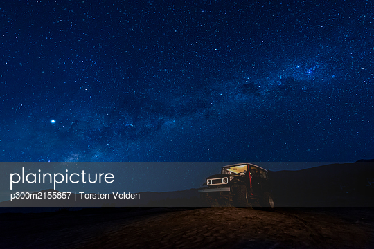 Indonesia, East Java, Milky Way galaxy on blue starry night sky over car parked in Bromo Tengger Semeru National Park - p300m2155857 by Torsten Velden