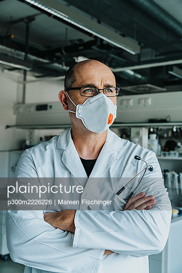 Scientist wearing face mask looking away while standing with arms crossed at laboratory - p300m2226226 by Mareen Fischinger