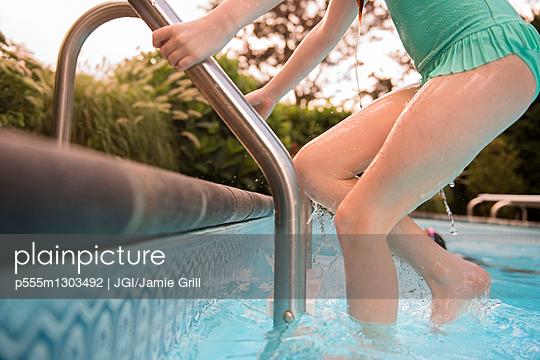 Caucasian girl exiting swimming pool - p555m1303492 by JGI/Jamie Grill